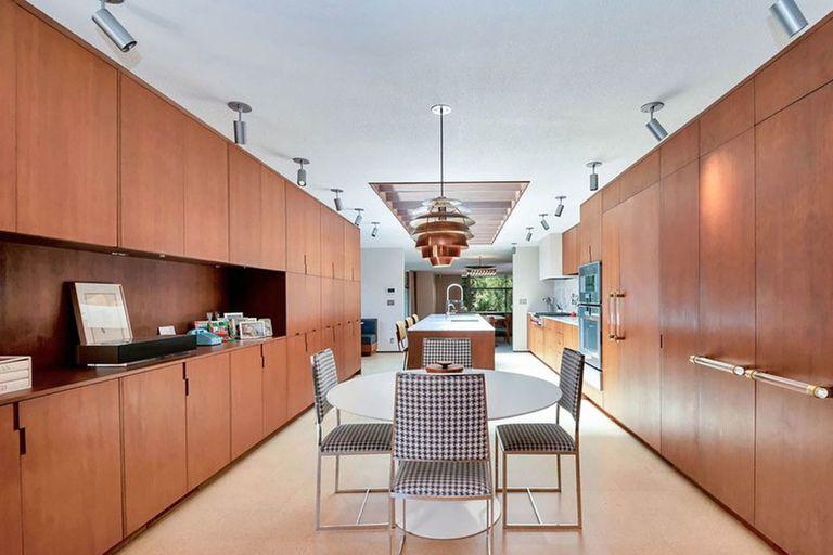 El sector que conecta el playroom con la cocina tiene muebles de madera y un tragaluz para aportar luz natural
