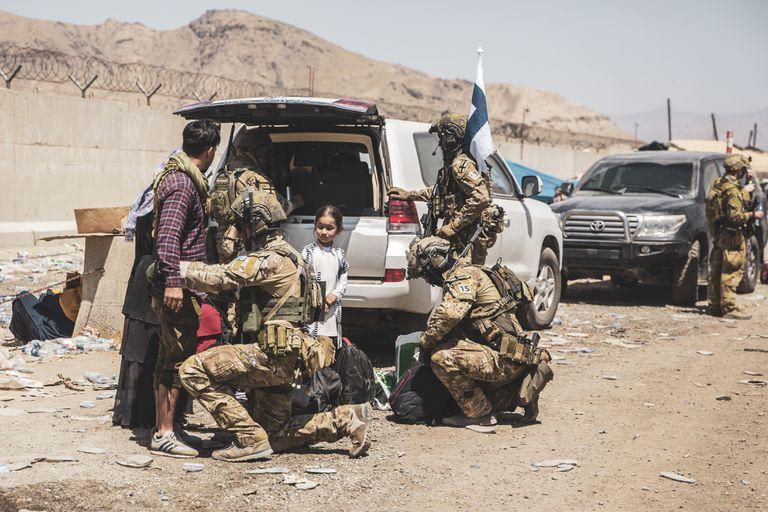 En esta imagen, distribuida por los Marines de Estados Unidos, soldados finlandeses de la coalición asisten a evacuados en controles en el aeropuerto internacional Hamid Karzai de Kabul, Afganistán, el 24 de agosto de 2021. (Sargento Victor Mancilla/Marines de Estados Unidos vía AP)