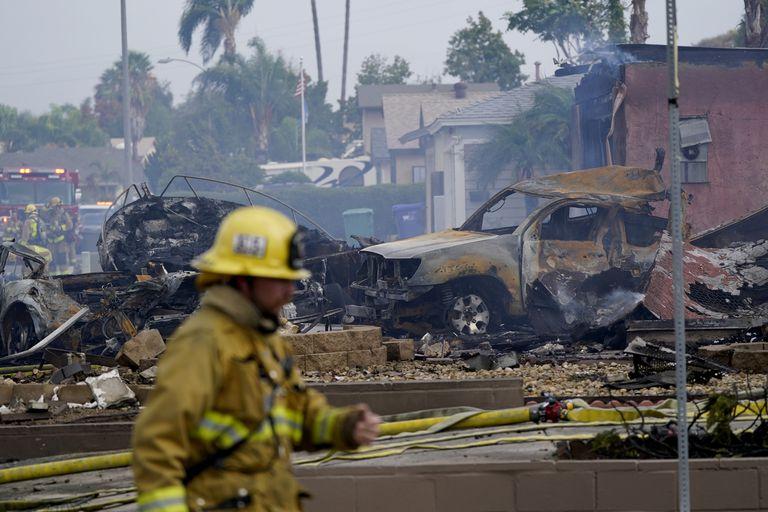 Cuadrillas de bomberos trabajan en el lugar en donde se estrelló una avioneta, el lunes 11 de octubre de 2021, en Santee, California. (AP Foto/Gregory Bull)