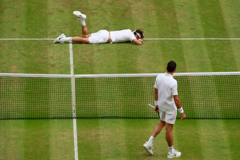 Una situación inusual: Federer, caído sobre el césped de Wimbledon, en las semifinales de 2016 ante Raonic. Sufrió problemas en la rodilla izquierda y luego se bajó de los JJOO de Río.