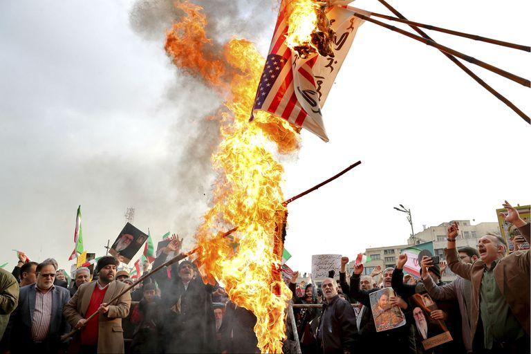 Manifestantes queman la bandera de Estados Unidos durante una manifestación a favor del gobierno después de las protestas por el aumento en el precio del combustible