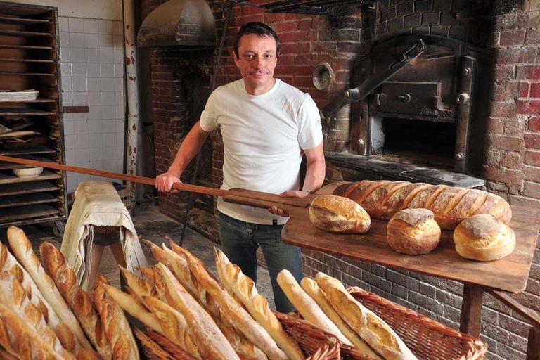 Bruno Guillot preparando pan en el horno de 1911, que es parte de su local L'epi