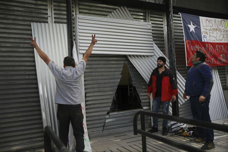 Trabajadores arreglan una cortina de hierro que protege a un banco, después de que se cortó un agujero triangular en la cortina en un intento de saqueo durante las protestas