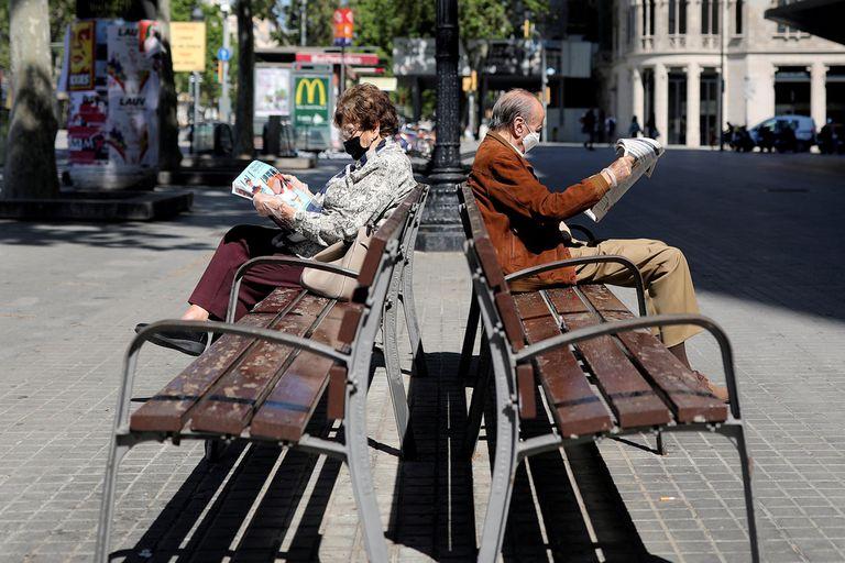 Dos adultos mayores durante las horas en que pueden estar al aire libre, en Barcelona.