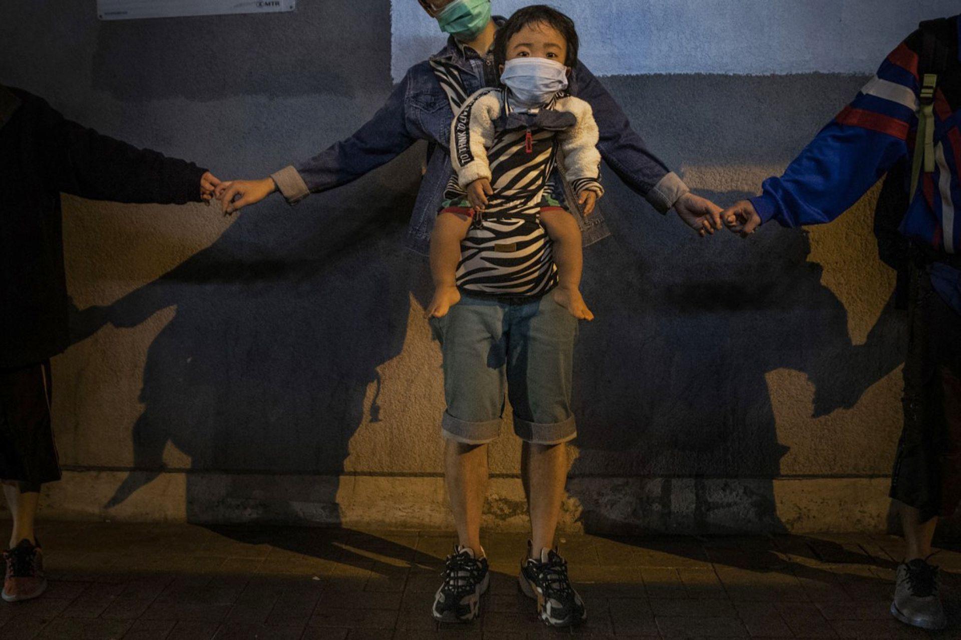 Un hombre carga a un niño mientras forma una cadena humana de solidaridad en Kowloon Bay, Hong Kong