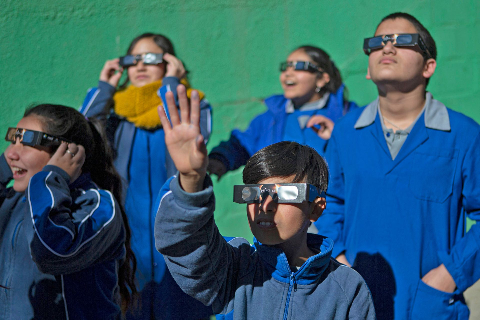 Un grupo de niños se prueba anteojos especiales para ver el eclipse