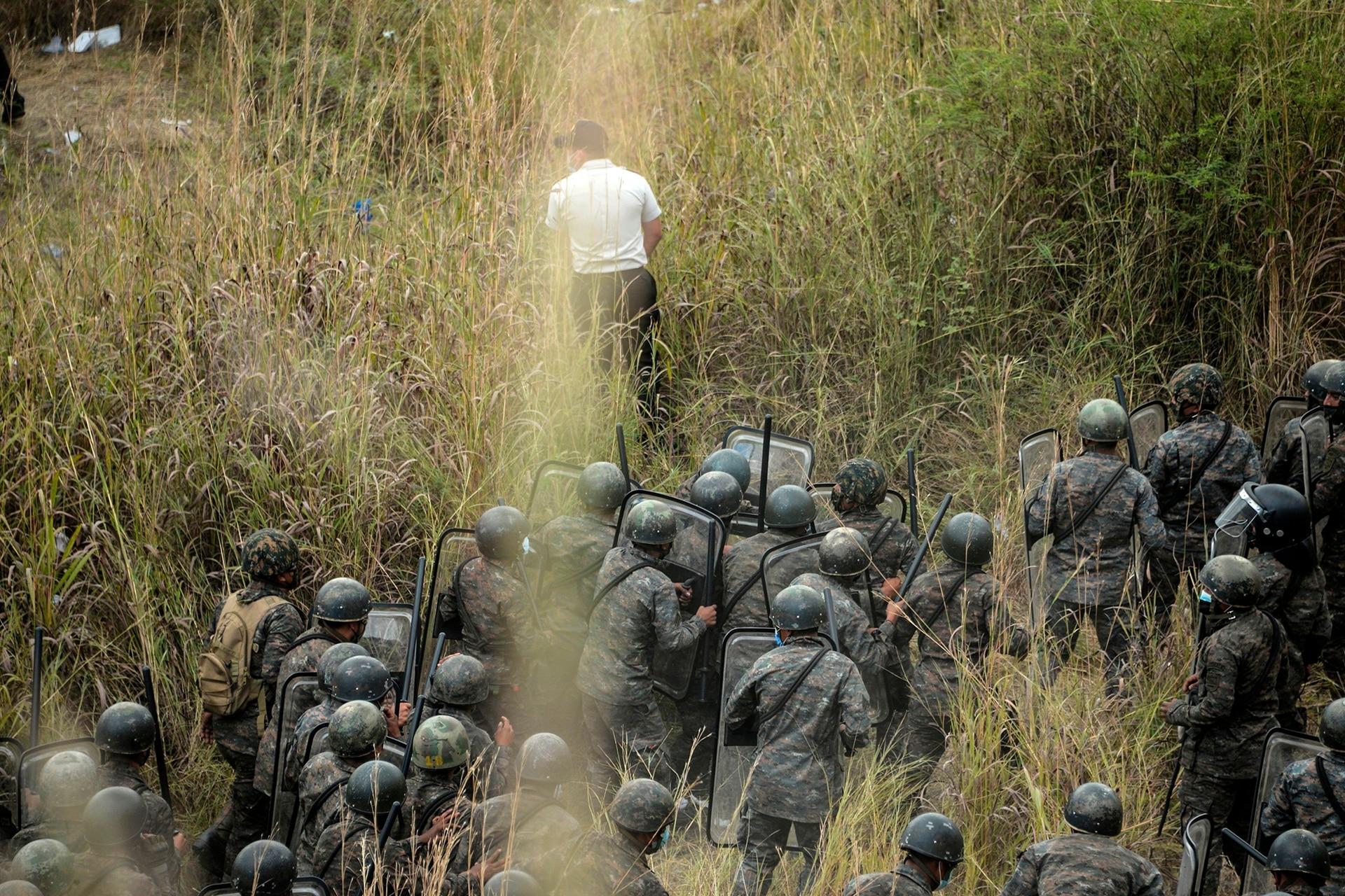 Fuerzas de seguridad bloquean a migrantes que llegaron en caravana desde Honduras en su camino a Estados Unidos, en Vado Hondo, Guatemala