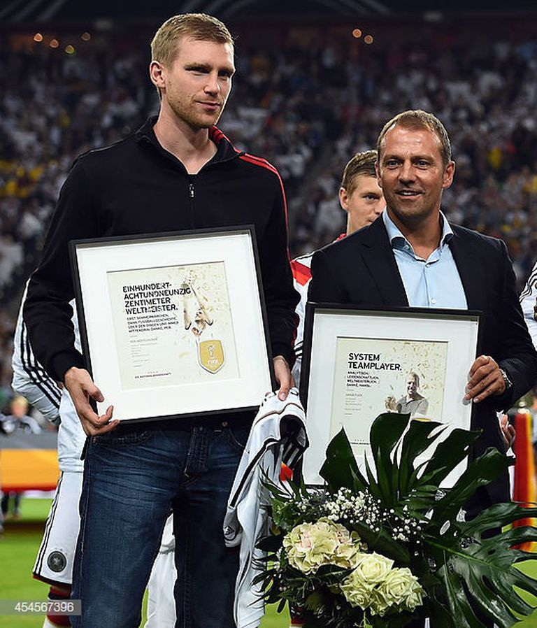 Hansi Flick con Mertesacker, a quien le explicó los motivos por los que quedó fuera de un partido importante en el Mundial 2014.