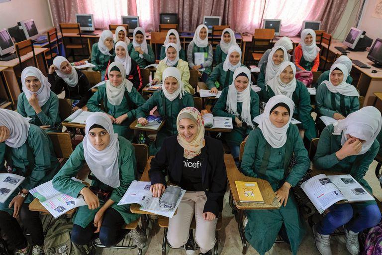 Arriba, en una escuela con refugiadas sirias en Jordania