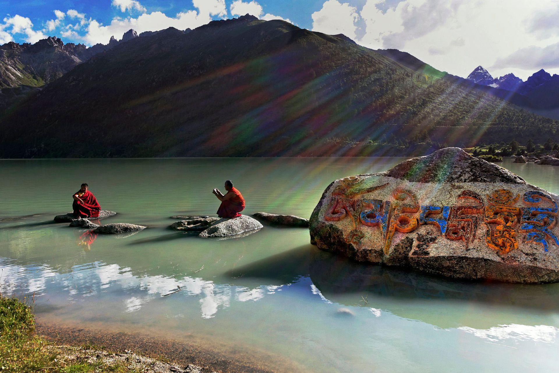 Dos monjes tibetanos en las orillas del lago Yilung Lhatso en el este del Tíbet. El grabado en la roca dice Om Mani Padme Hum, que es el mantra del Buda de la Compasión