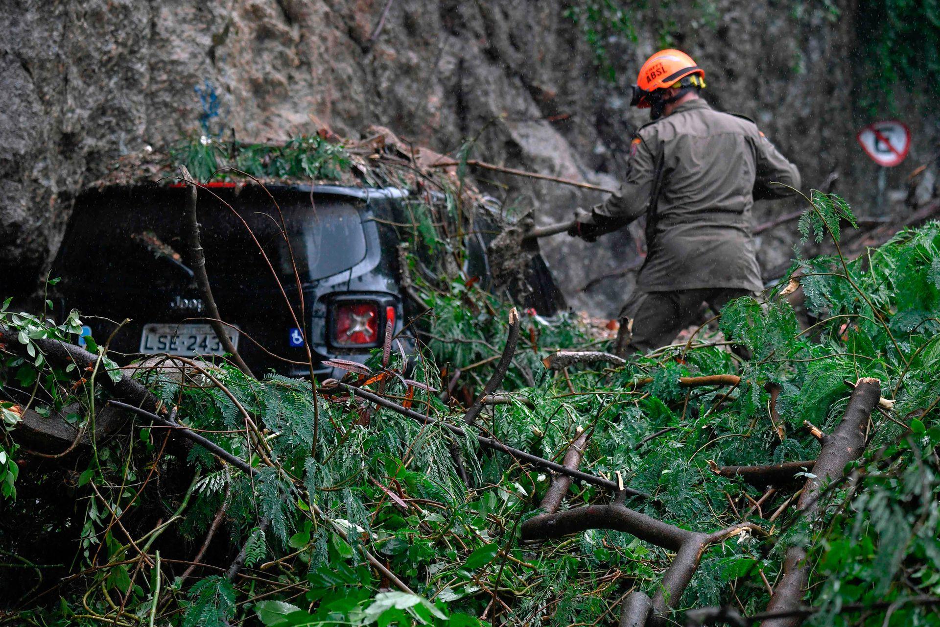 Un rescatista trabaja en la recuperación de un automóvil luego de un deslizamiento de tierra provocado por fuertes lluvias y que afectó a la ciudad desde la noche de ayer, inundando varias áreas de la ciudad de Río de Janeiro, en Brasil