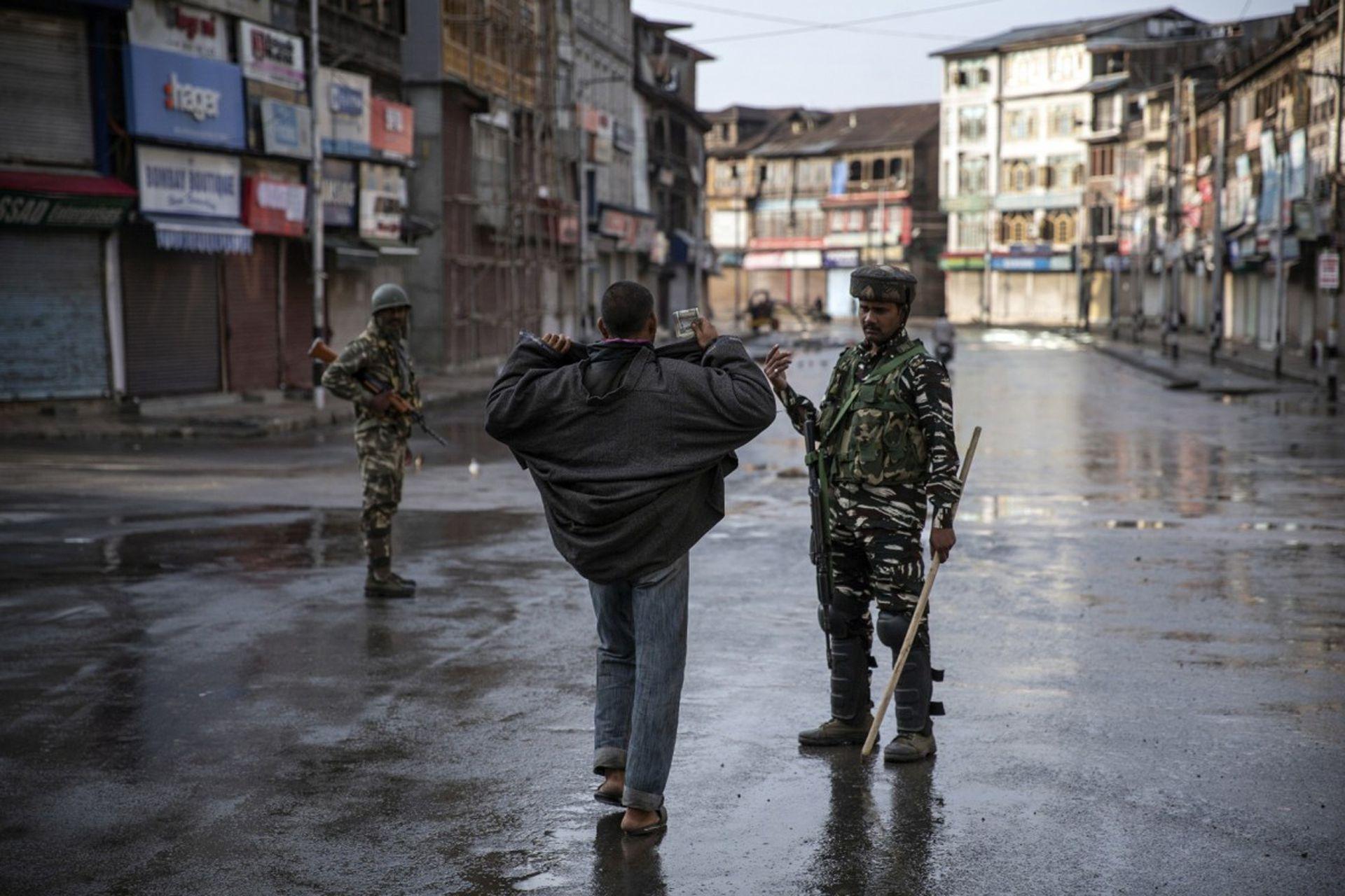 Un soldado paramilitar indio le ordena a un cachemir abrir su chaqueta antes de registrarlo durante el toque de queda en Srinagar