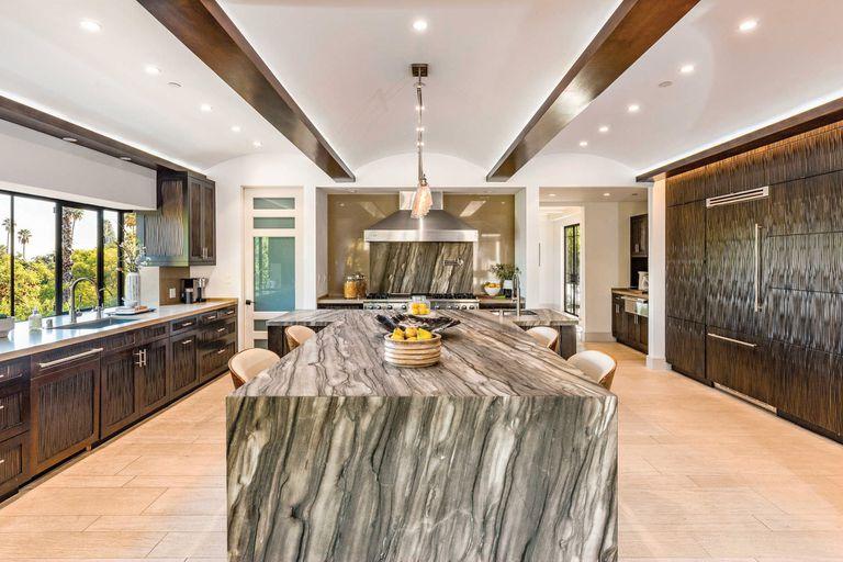La cocina, con muebles de madera oscura y una enorme isla de mármol.