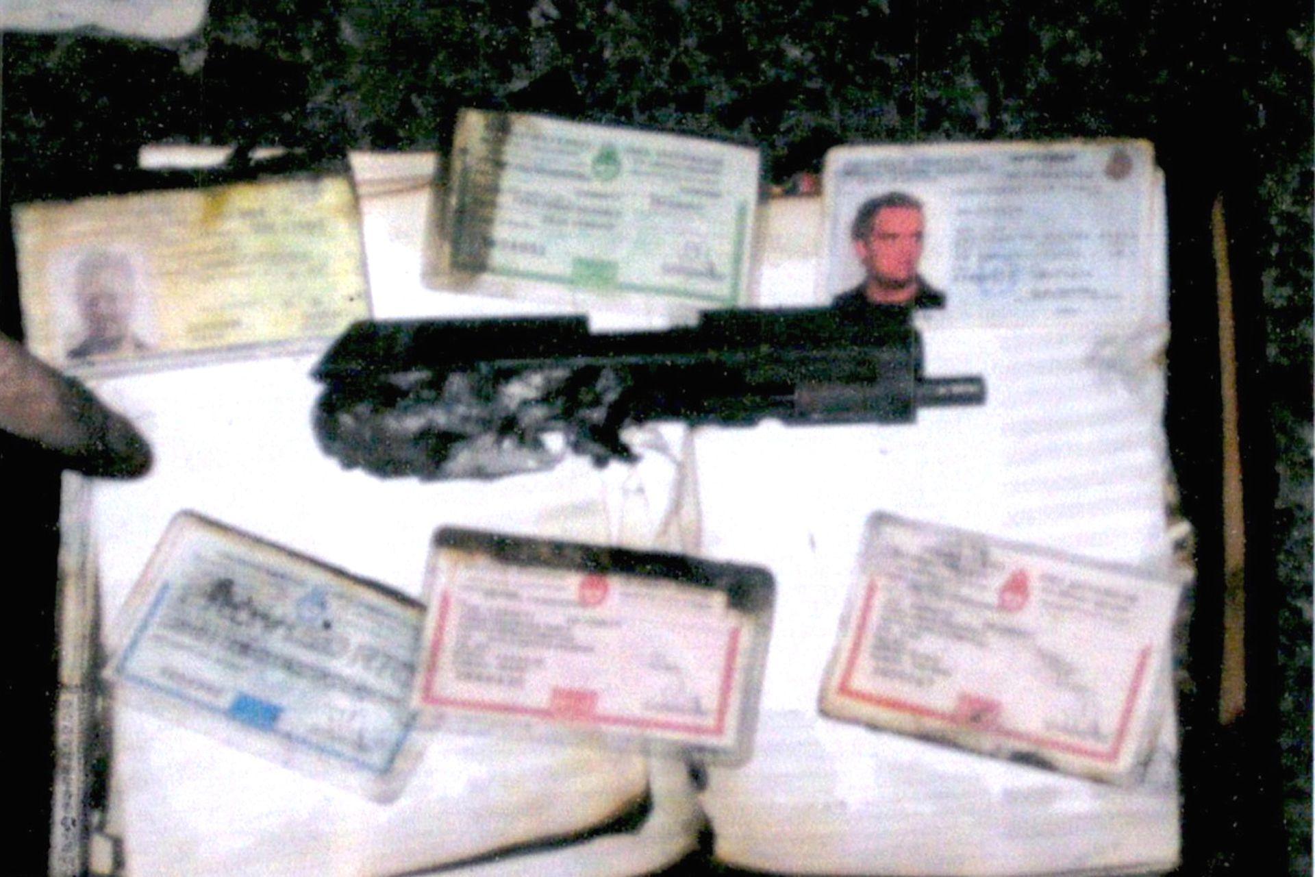El cañón de una de las pistolas de Sebastián Forza, destruida por el fuego dentro de la camioneta, y documentación de las víctimas
