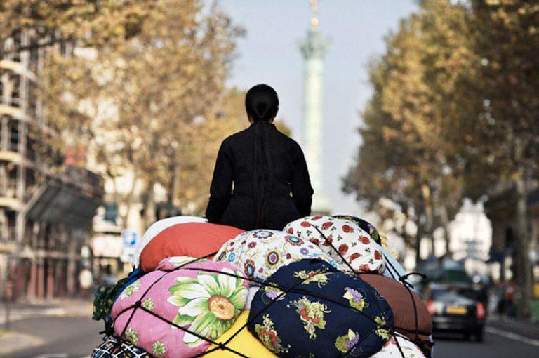 """En fotos y videos de sus performances, Kimsooja suele aparecer de espaldas al observador, a bordo de un vehículo cargado de """"bottaris"""""""