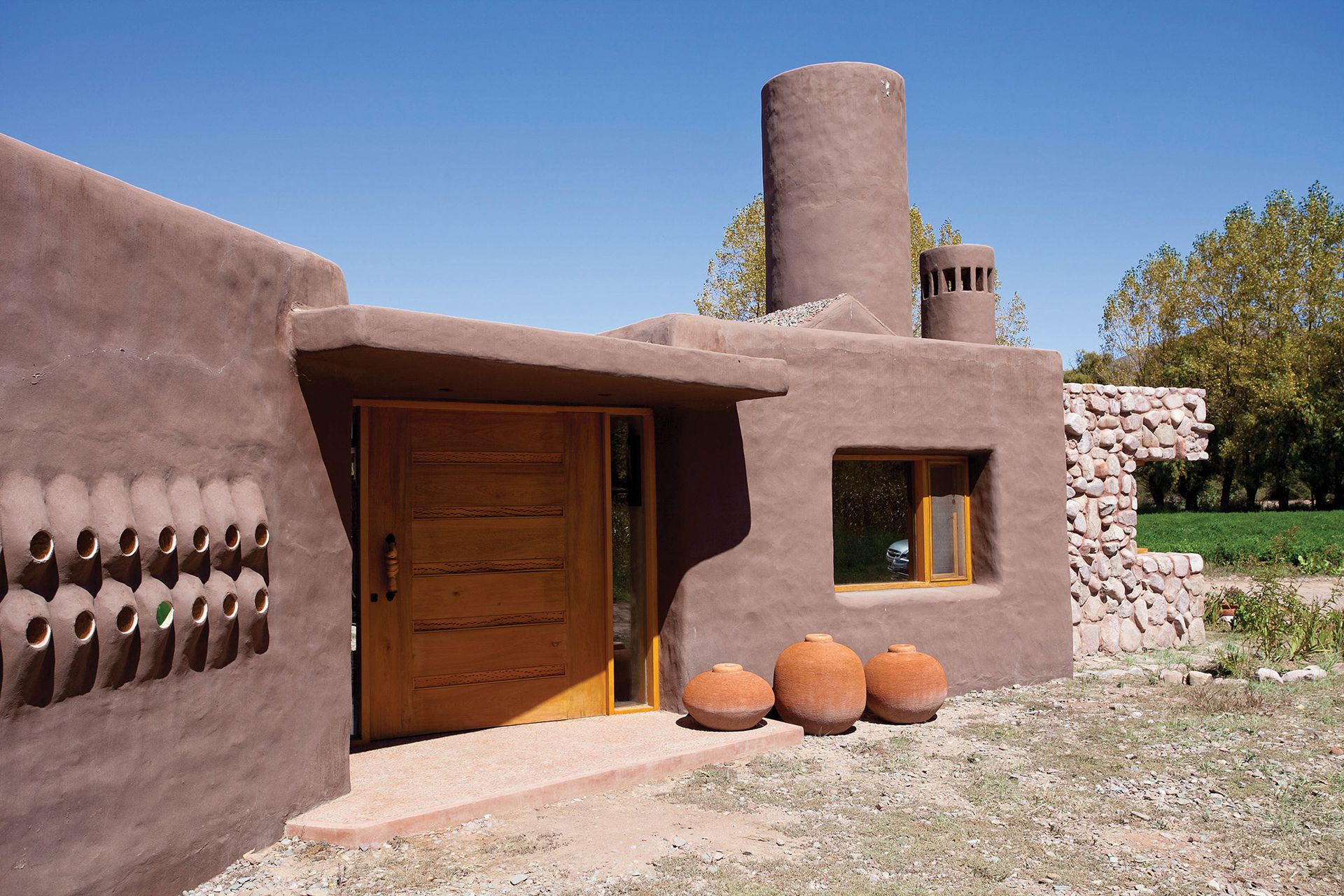 Una fachada con los colores de la tierra y formas orgánicas.