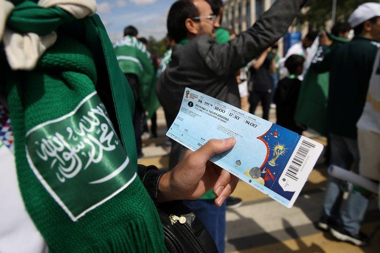 Un espectador muestra la entrada al partido ianugural entre Rusia Arabia y Saudita