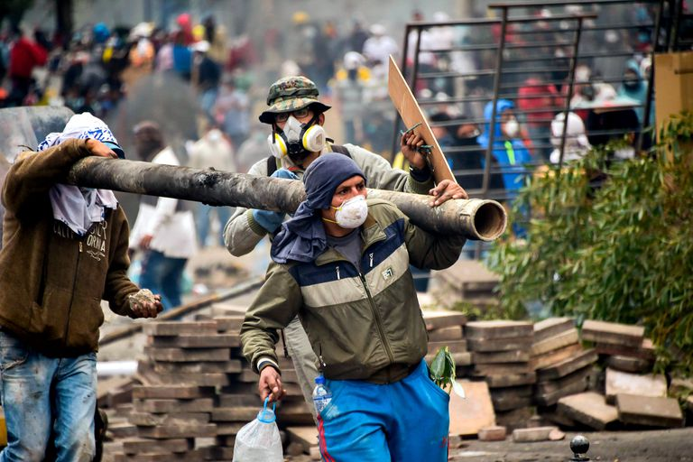 Manifestantes cargan un tubo durante el enfrentamiento con la policía