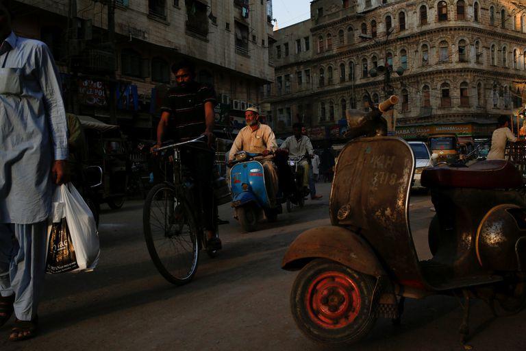 Un hombre monta una Vespa en una calle en un barrio en Karachi