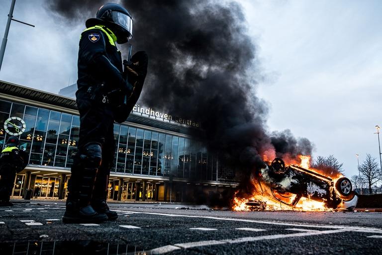 Un coche fue incendiado frente a la estación de tren, el 24 de enero de 2021 en Eindhoven, luego de una manifestación de varios cientos de personas contra las políticas para frenar el coronavirus