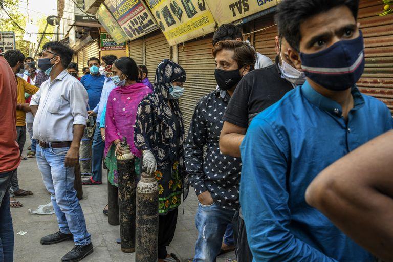La gente hace fila con tubos de oxígeno para cambiarlos para recargarlos en una tienda al sur de Delhi. Casi la mitad de la demanda de oxígeno médico mundial se concentra en la India