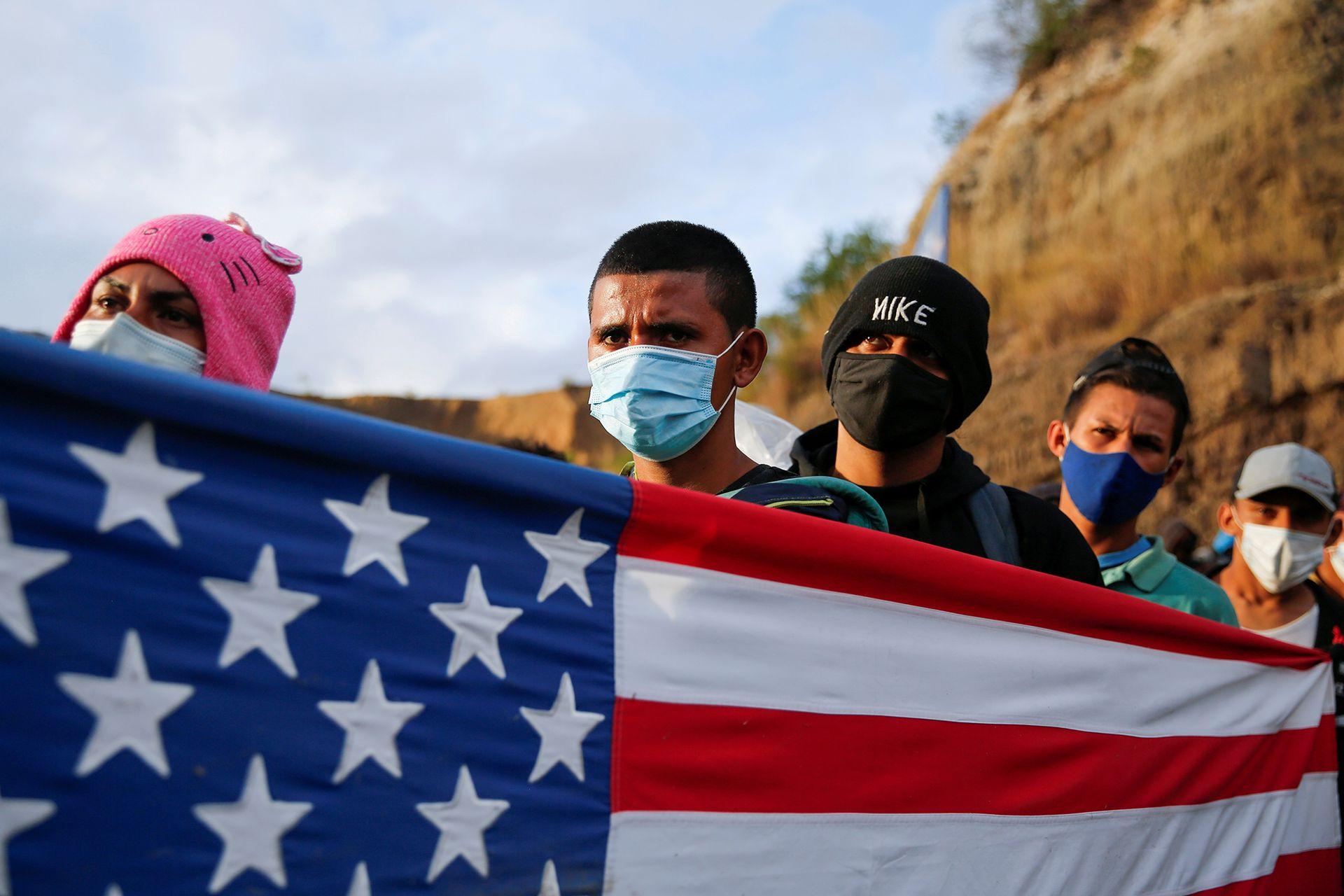 Migrantes Hondureños con la bandera de Estados Unidos