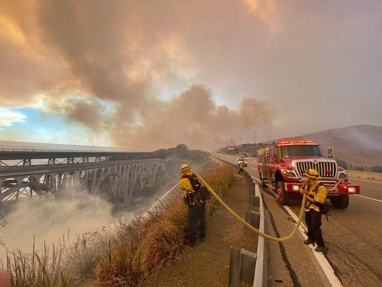 En esta fotografía facilitada por el Departamento de Bomberos del Condado Santa Bárbara, bomberos combaten flamas de un incendio forestal el martes 12 de octubre de 2021 por la tarde en el borde de la carretera 101 en dirección sur en Vista Point, al norte de Refugio State Beach, en el condado Santa Barbara, en California. (Mike Eliason/Departamento de Bomberos del Condado Santa Barbara vía AP)