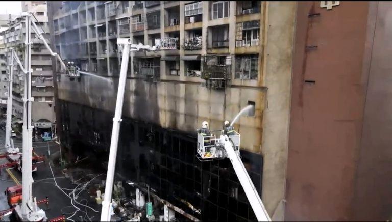 En esta imagen tomada de un video del medio taiwanés EBC, bomberos lanzando agua a un edificio incendiado en Kaohsiung, en el sur de Taiwán, el jueves 14 de octubre de 2021.  (EBC via AP )