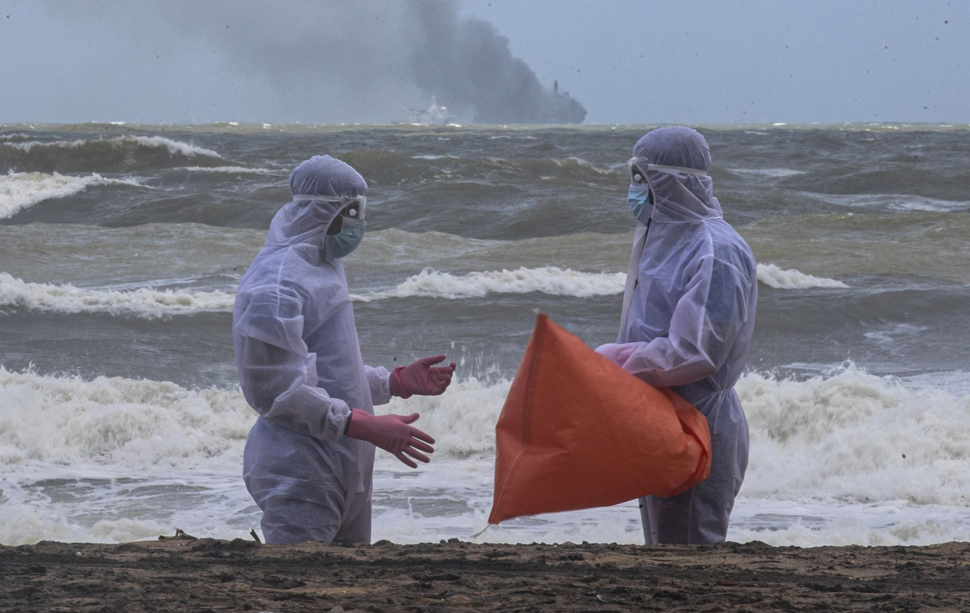 Soldados de la Armada de Sri Lanka vestidos con trajes protectores conversan mientras limpian los escombros arrastrados a la costa desde el barco de Singapur MV X-Press Pearl
