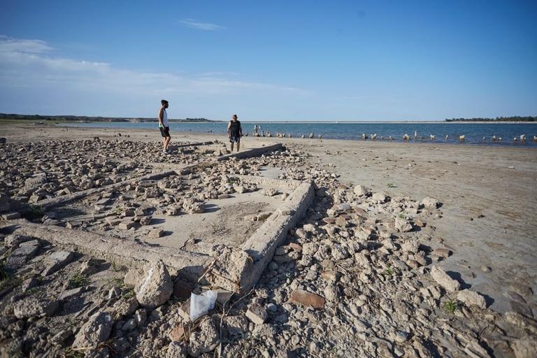 Miguel Torres y Marcos Tobar miran parte de la antigua finca que la baja del agua dejó al descubierto en el dique El Carrizal
