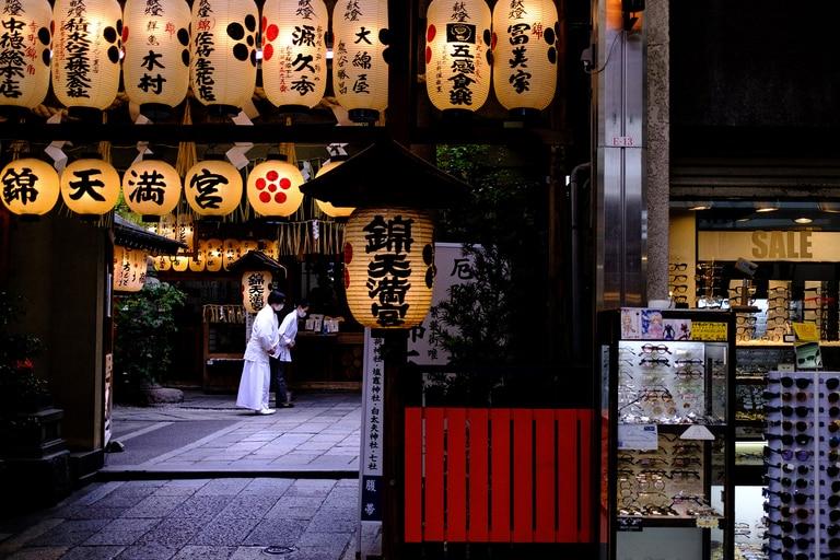 Personas con máscaras faciales dentro de un santuario cerca del mercado Nishiki de Kyoto el 22 de mayo de 2020