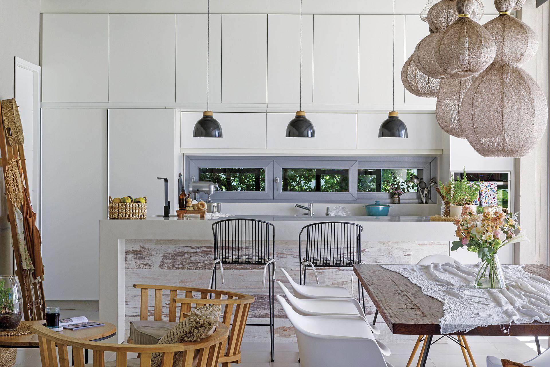 Perfectamente alineados, los muebles laqueados blancos (El Camino Studio) también alojan las heladeras y los hornos a ambos lados de la mesada.