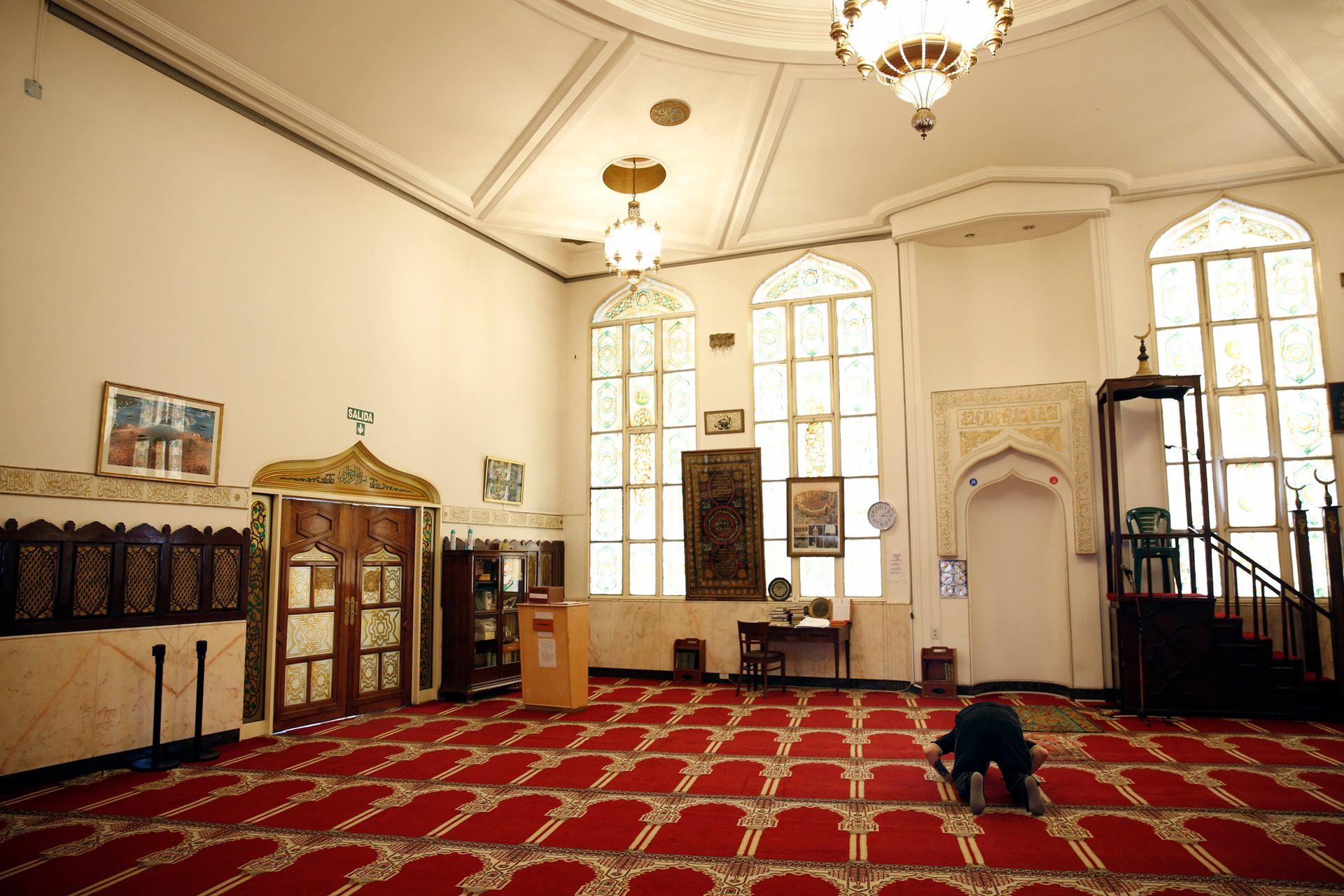 Un fiel realiza su oración frente a la quibla en el interior de la mezquita