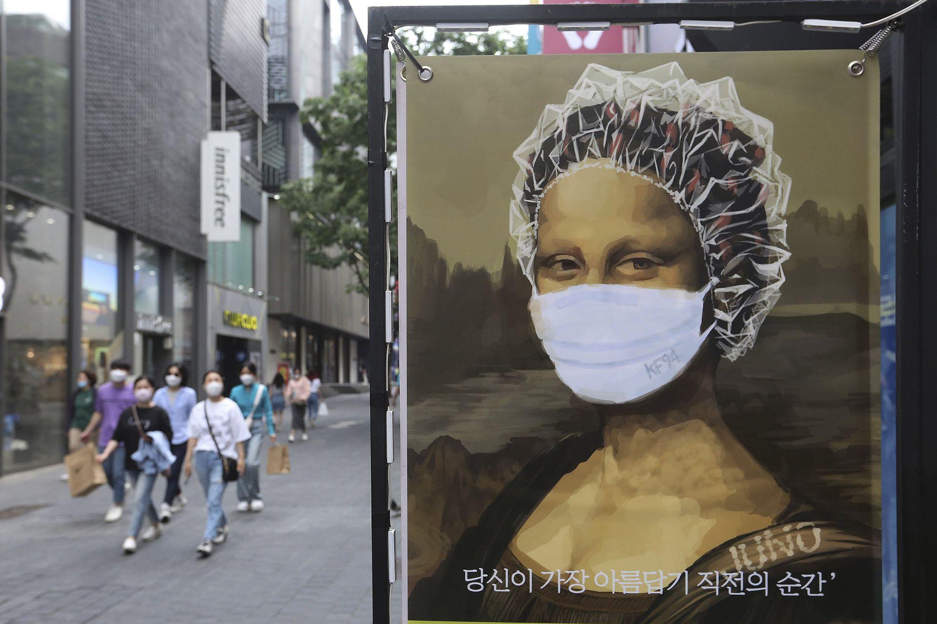 Hasta la Mona Lisa en un afiche publicitario de una peluquería usa barbijo en las calles de Seúl, Corea del Sur