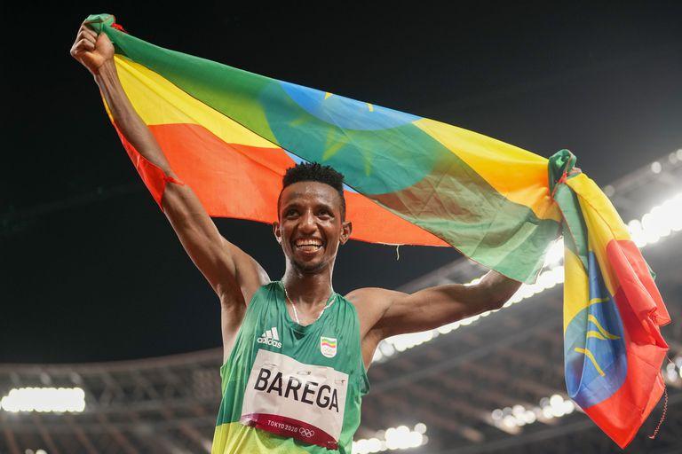 El etíope Selemon Barega celebra con la bandera de su país luego de ganar la medalla de oro en los 10.000 metros en Tokio 2020.