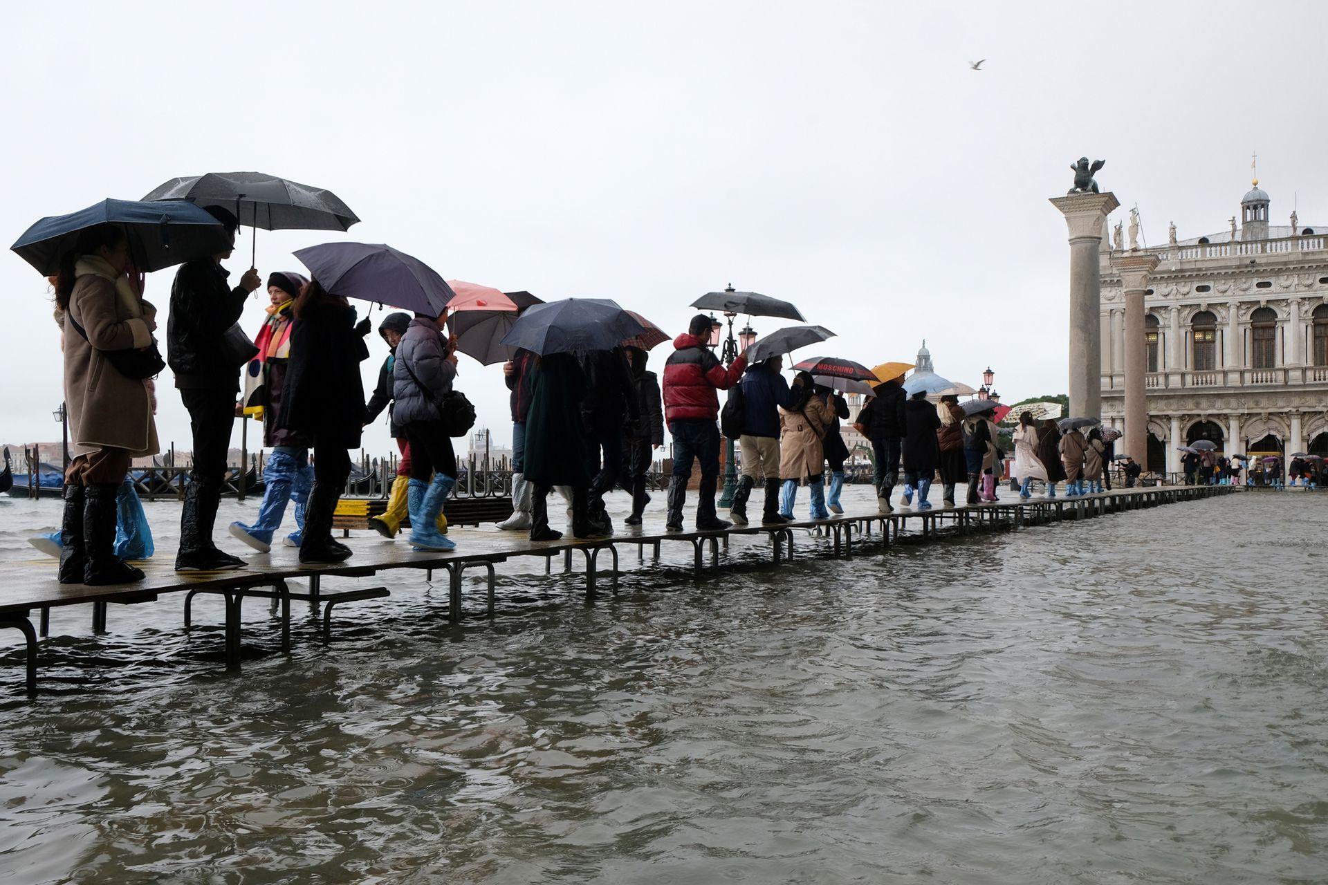 Varias personas cruzan la plaza sobre la pasarelas