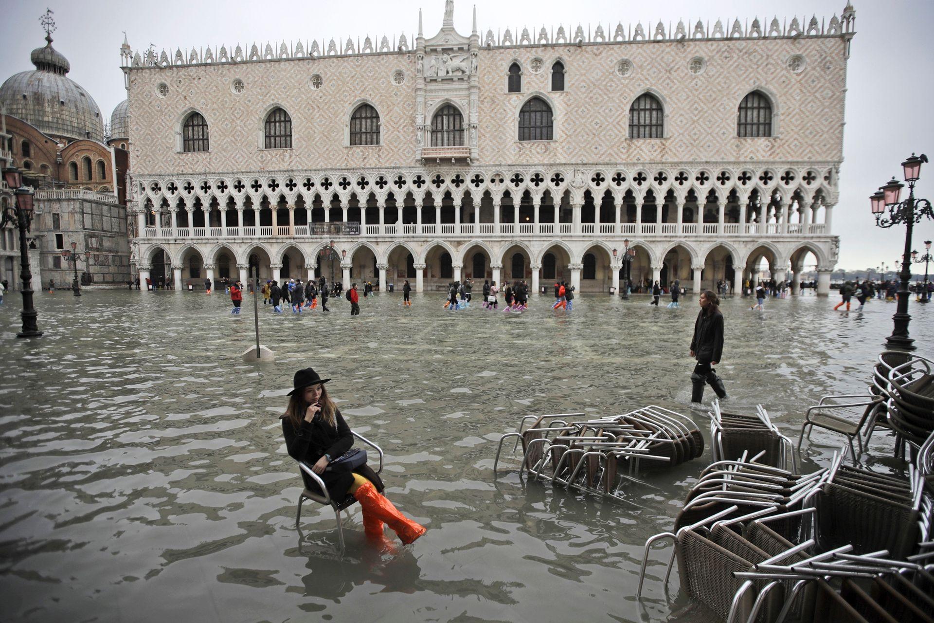 Una mujer se sienta en una silla en una plaza inundada de San Marcos, en Venecia, el 13 de noviembre de 2019