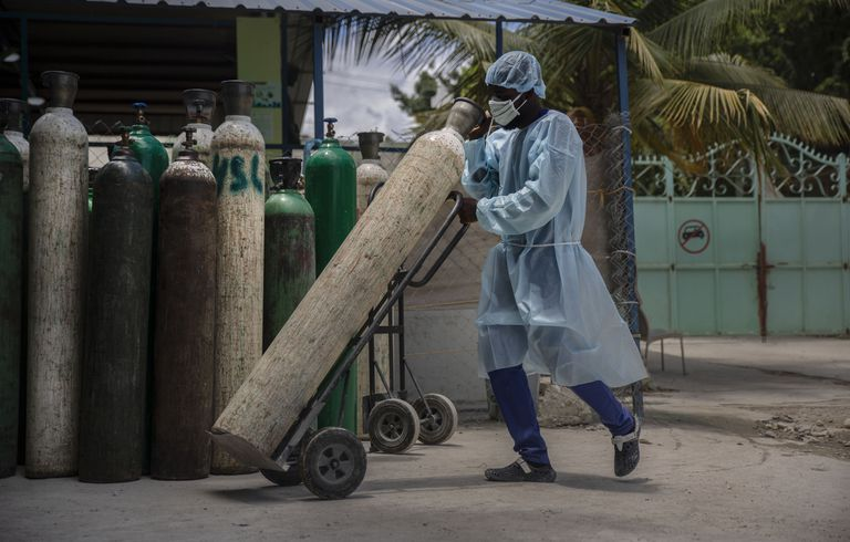 ARCHIVO - En esta fotografía de archivo del 5 de junio de 2021, un empleado de hospital con equipo para protegerse del COVID-19 transporta tanques de oxígeno en Puerto Príncipe, Haití. (AP Foto/Joseph Odelyn, archivo)