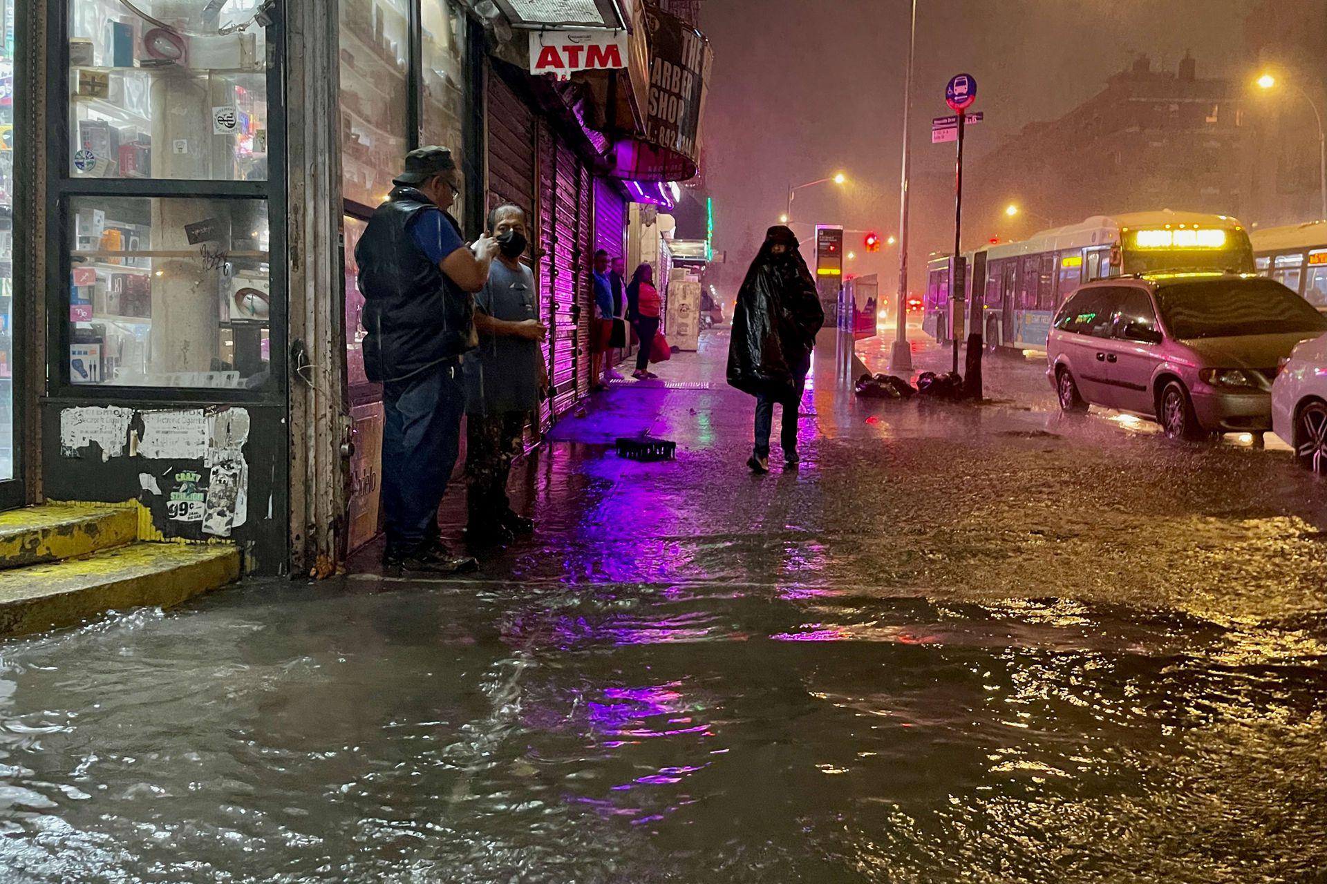 Algunas personas tratan de seguir su camino en el Bronx, pese a las constantes lluvias.