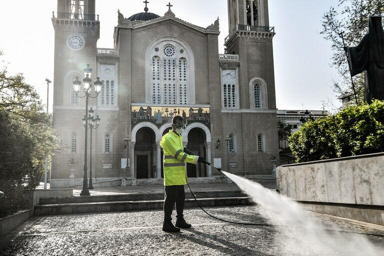Un trabajador municipal desinfecta la explanada frente a la Iglesia Metropolitana de Atenas el 15 de abril de 2020, mientras el país permanece bajo cuarentena para detener la propagación de la pandemia de coronavirus