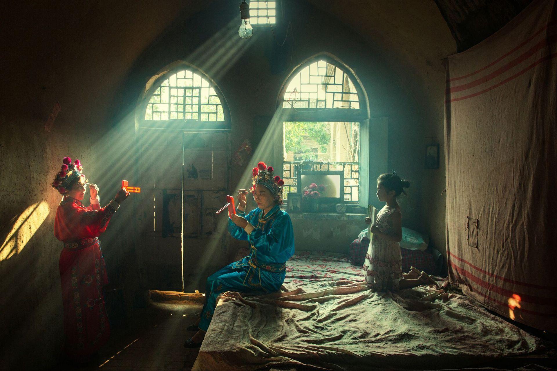 Primer lugar, categoría Personas, la imagen es de Huaifeng Li, actores se preparan para una ópera vespertina en el condado de Licheng, China
