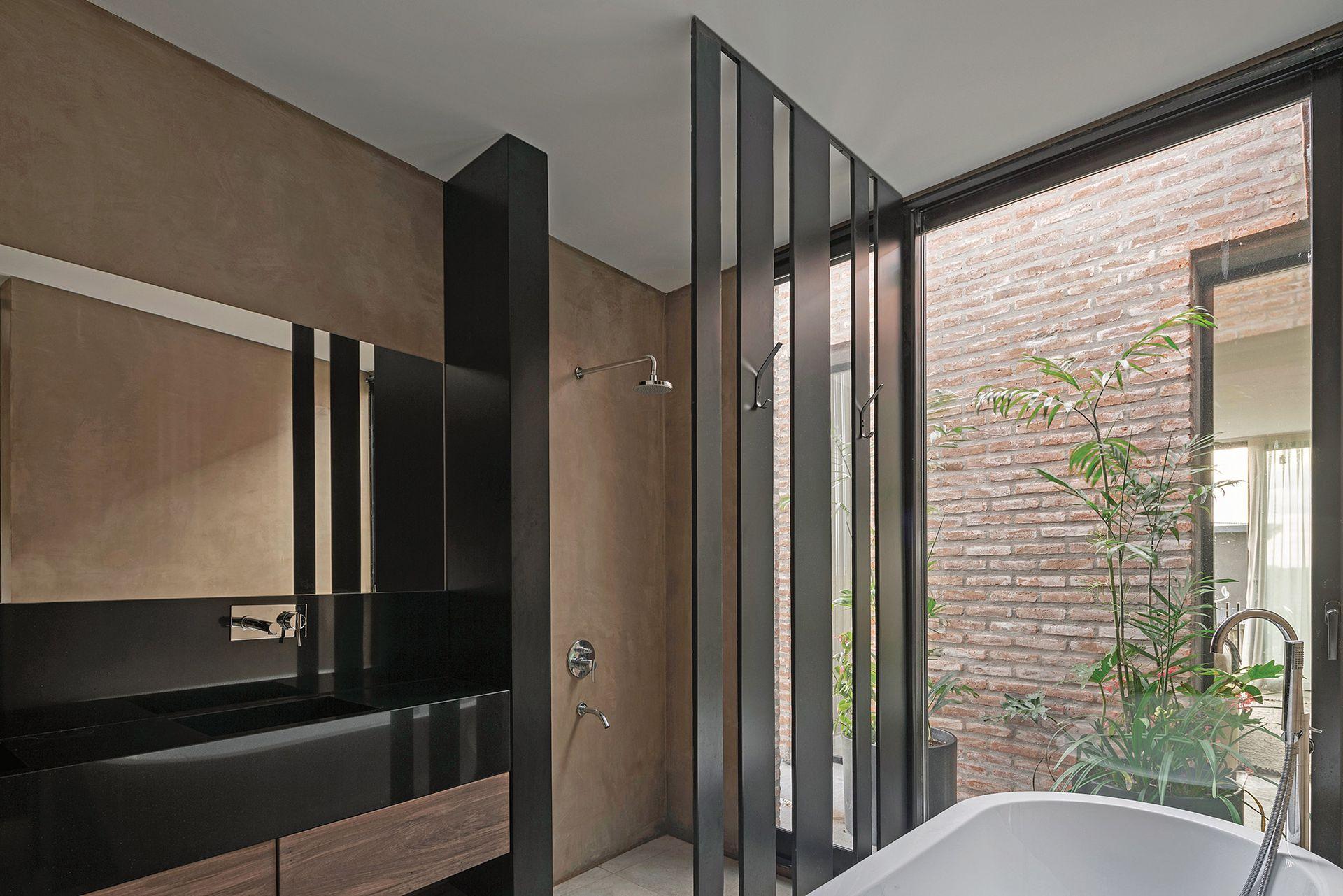 El baño tiene revestimiento en estuco color visón (Tarquini) y mueble de petiribí con mesada en mármol negro Brasil. A modo de mampara, un panel con tiras de hierro laqueado.
