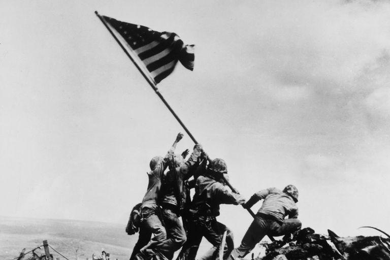 Marines y un médico de la Armada alzan la bandera estadounidense en la batalla de Iwo Jima.