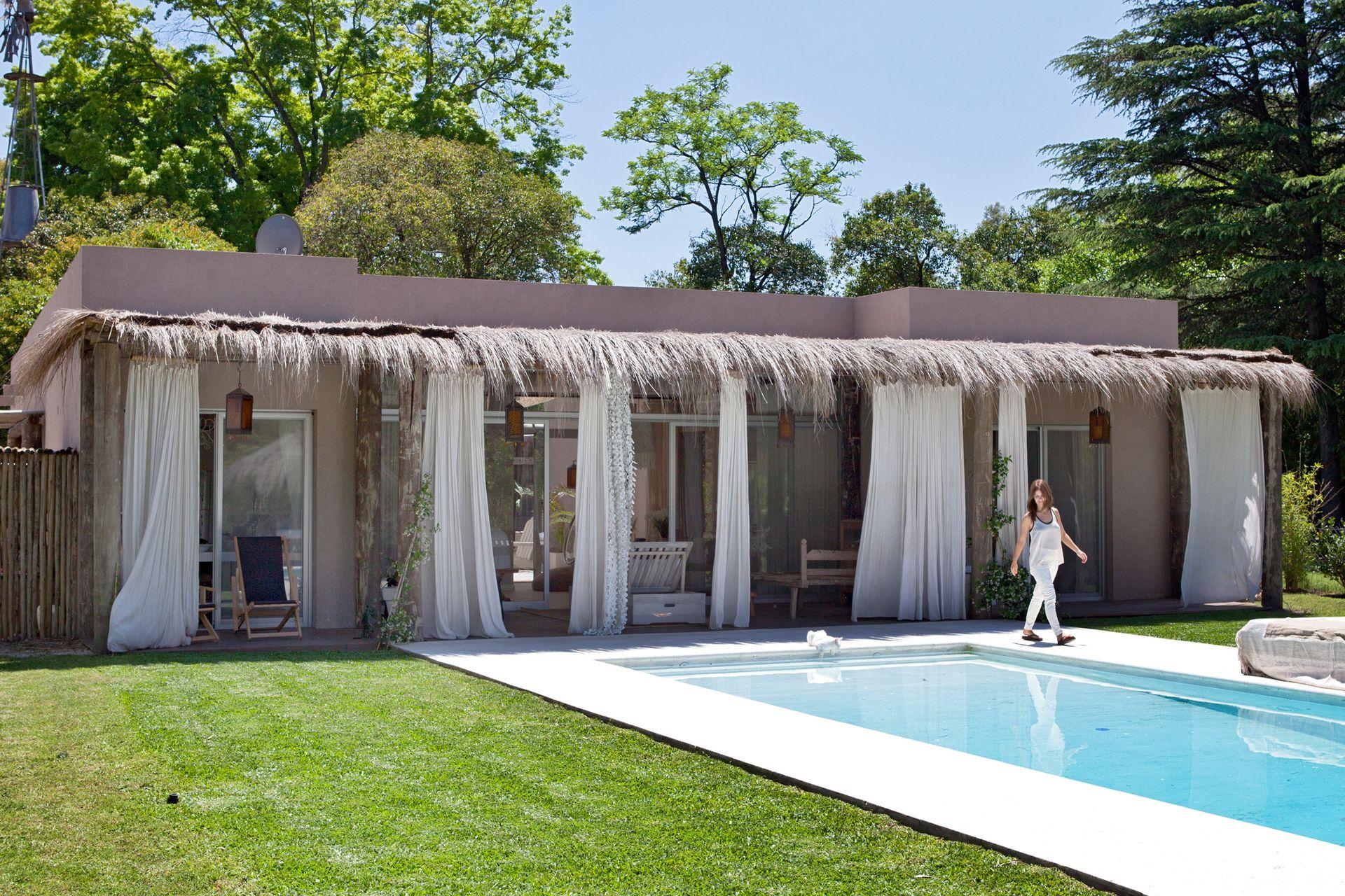 La galería de Florencia Pichon Rivière, creadora de Tiki House, está protegida por un techo de cañas y cortinas de lino.