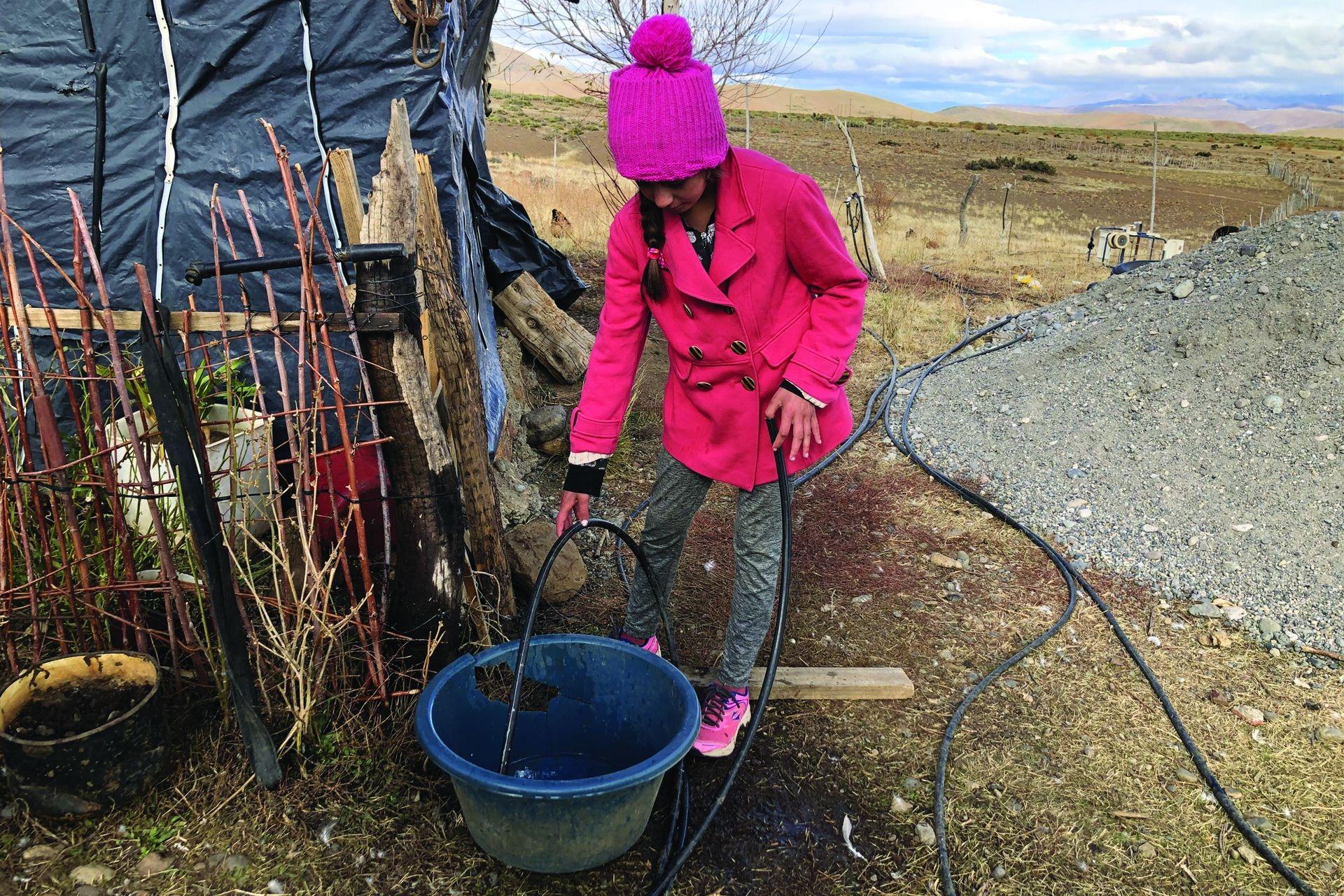 Maciela llena el balde de agua para darle de tomar a las chivas guachas; la familia necesita un tanque australiano para almacenar la poca agua que les llega de una vertiente