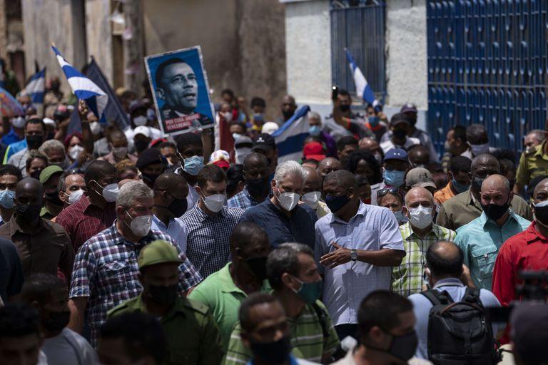 El presidente de Cuba, Miguel Díaz Canel, camina con sus seguidores después de una protesta contra el gobierno en San Antonio de los Baños, Cuba.