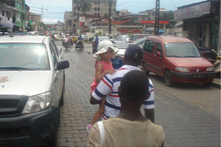 En en mercado central en Douala, junto a su hija en brazos, detrás un changarín lo secunda