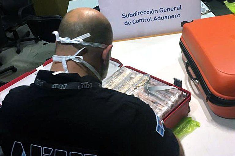 Un agente de Aduana de Ezeiza con las valijas que contenían la droga