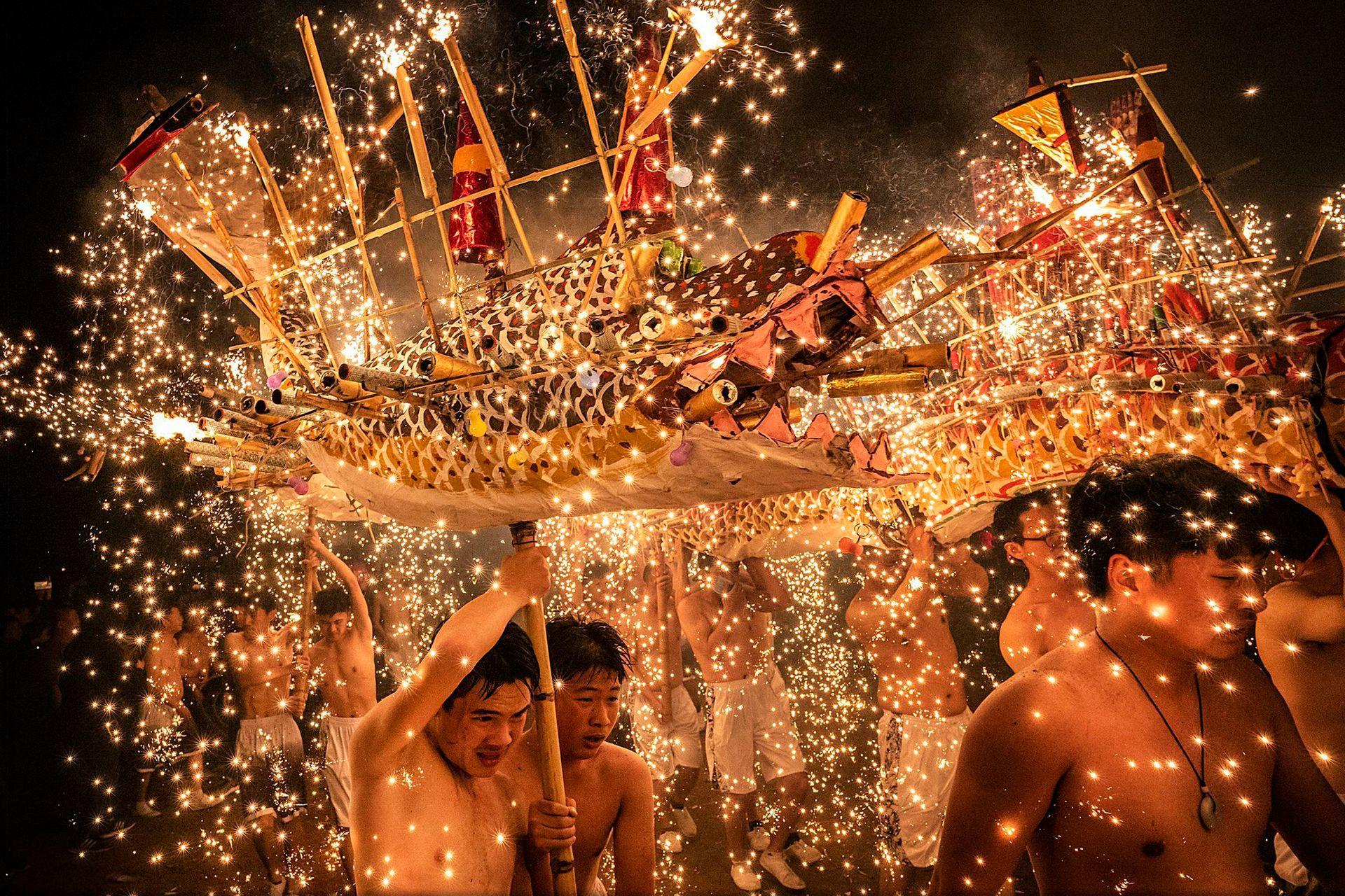 Elección de la gente, Categoría Gente, la imagen es de Léo Kwok, varias personas en Meizhou, China, realiza una danza del dragón de fuego, bañada por chispas de hierro fundido que arrojan fuegos artificiales para celebrar el Festival de los Faroles