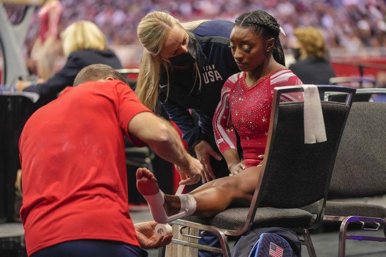 Simone Biles recibe atención de sus asistentes en el Trial norteamericano de gimnasia